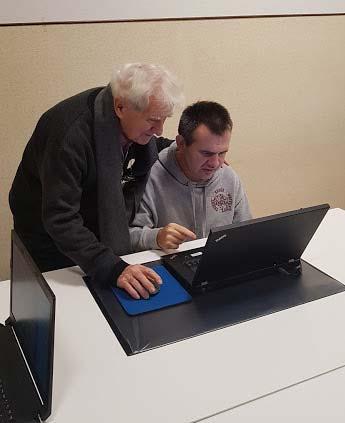 Insegnante mostra a persona con disabilità come utilizzare il computer per comunicare, grazie a Vie Di Luce